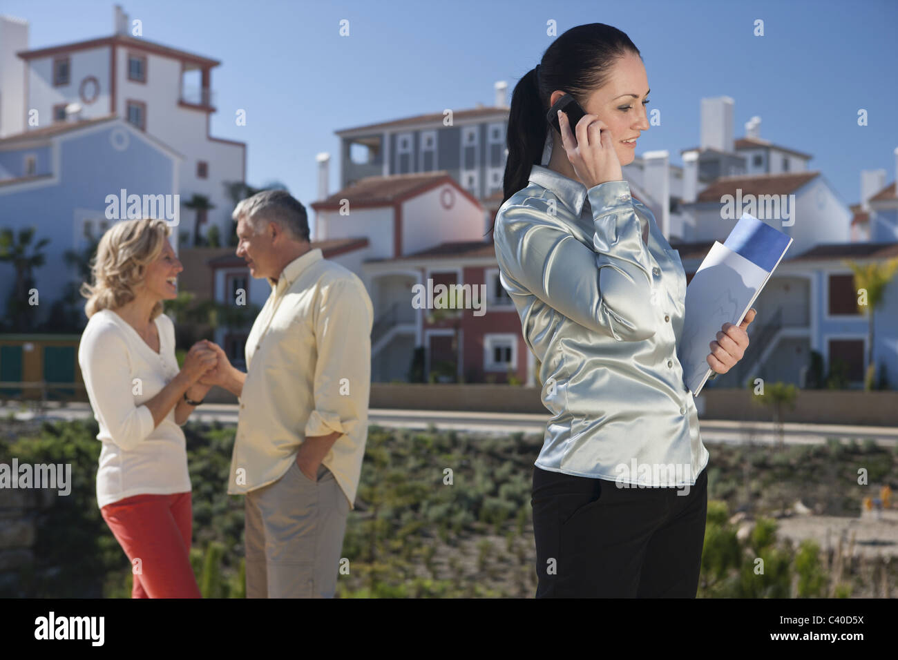 Realestate agent talking on mobile phone - Stock Image