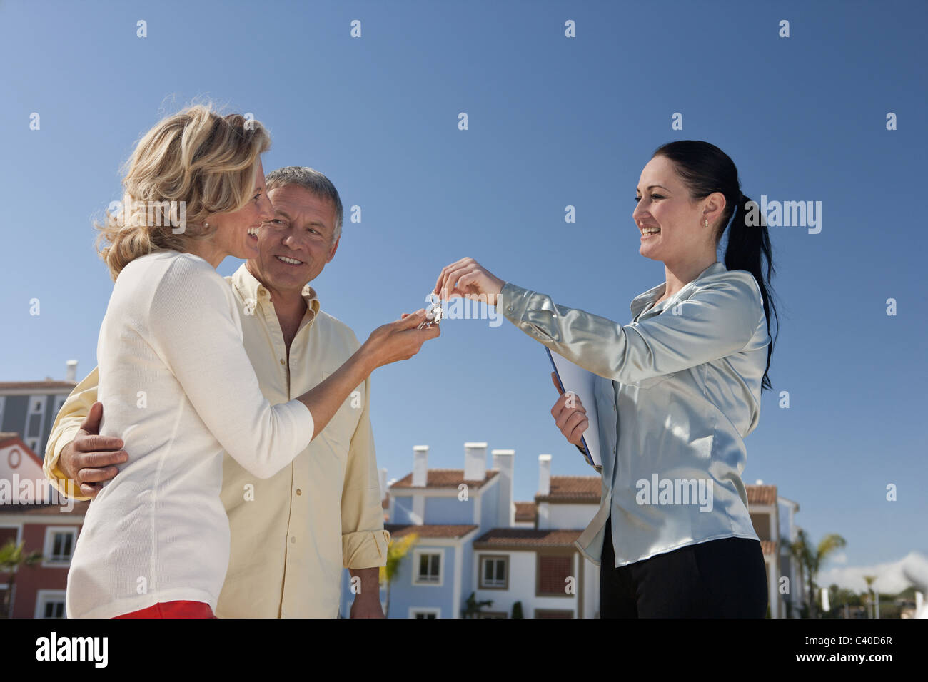 Realestate agent handing keys to couple - Stock Image