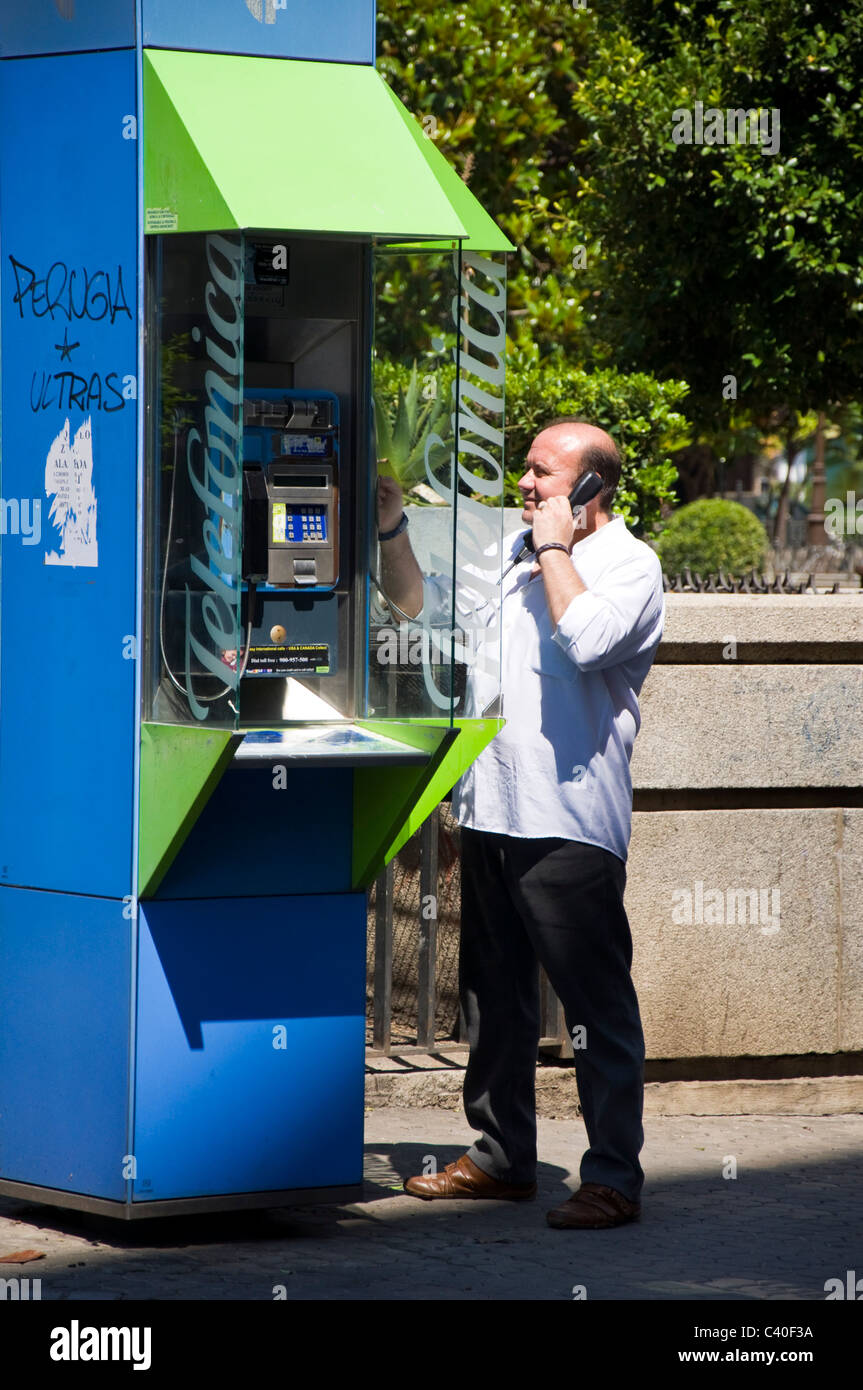 Man using public telephone in the city Telefonica SA - Stock Image