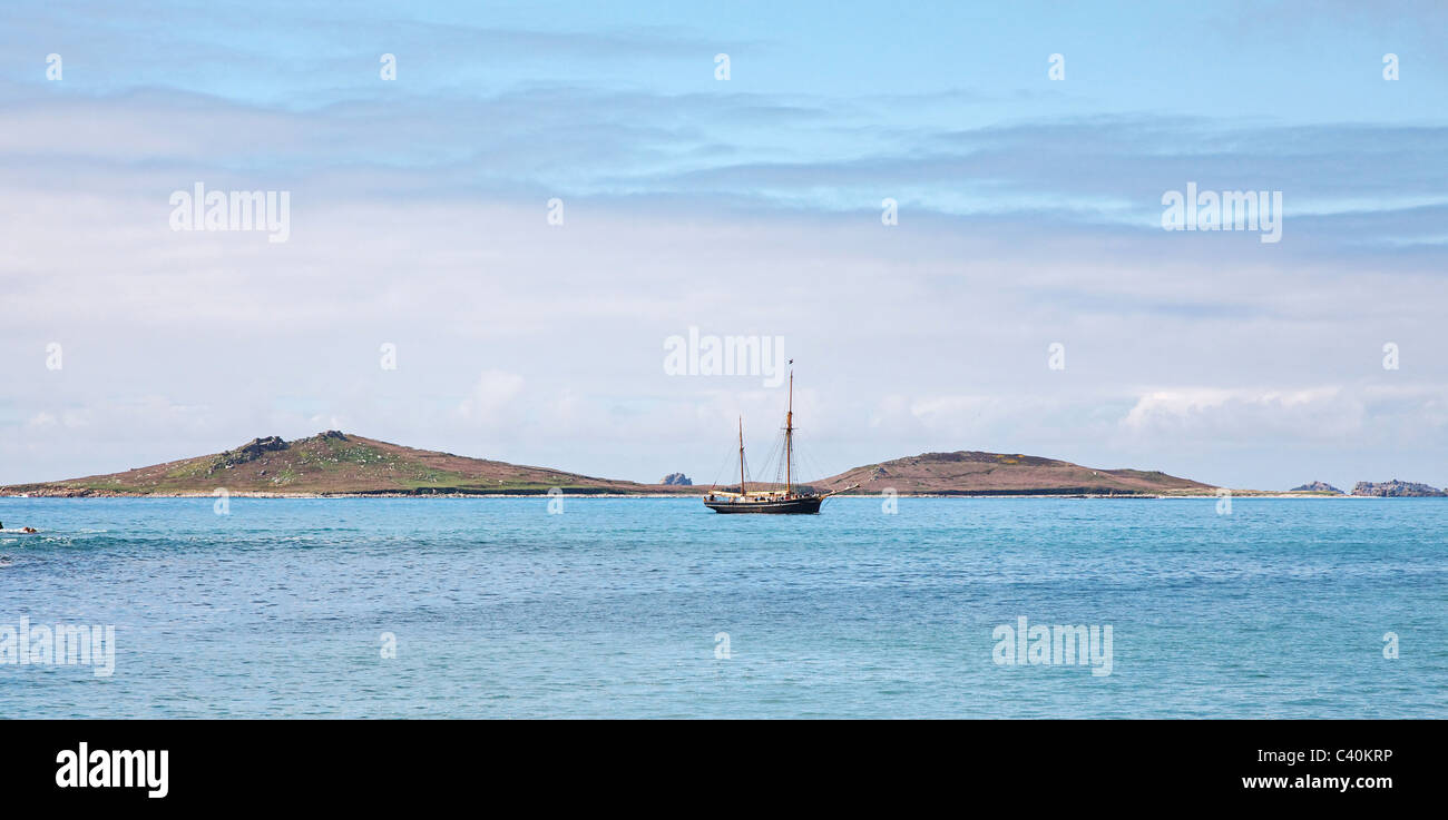 Double masted sailing vessel cruising past Samson island towards St Mary's in the Isles of Scilly Stock Photo