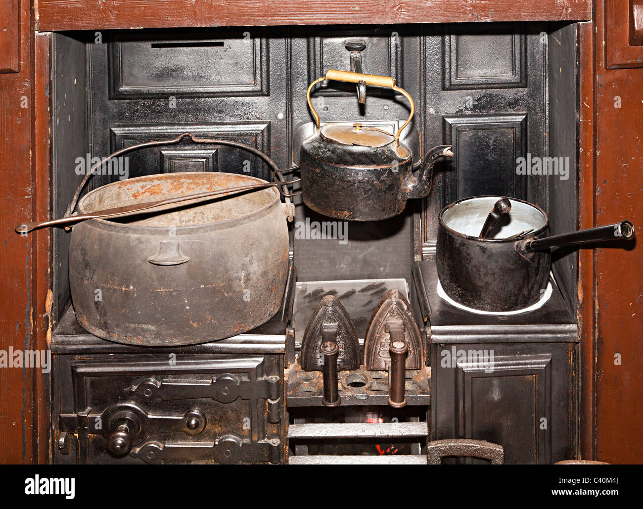 Saucepan kettle pot and irons on range in old kitchen Wales UK - Stock Image