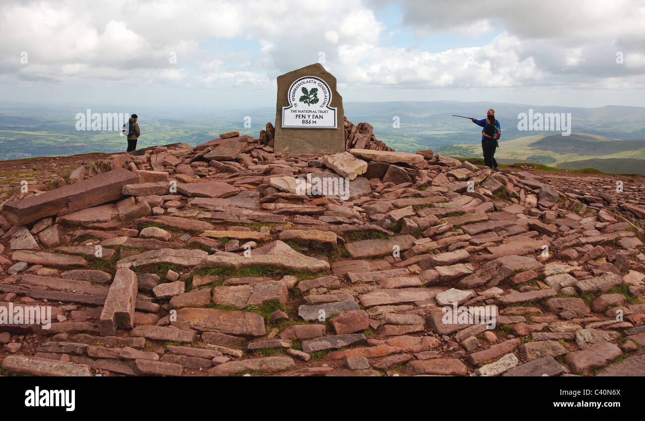 Walkers reaching the plaque crowning the old red sandstone summit cairn on Pen y Fan in the Brecon Beacons National - Stock Image