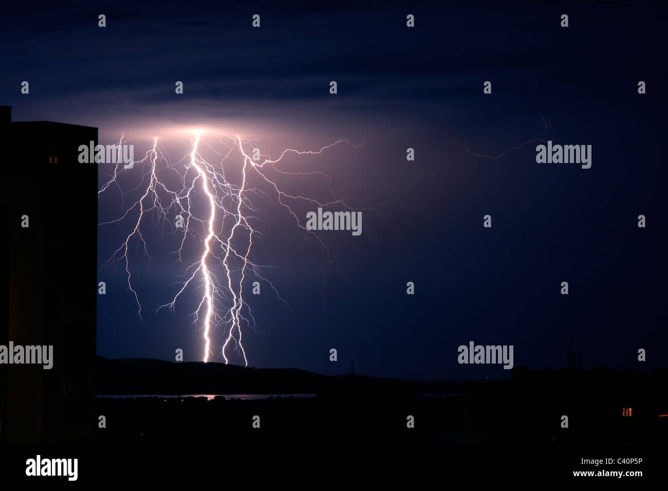 Lightning storm strikes over city and sea - Stock Image