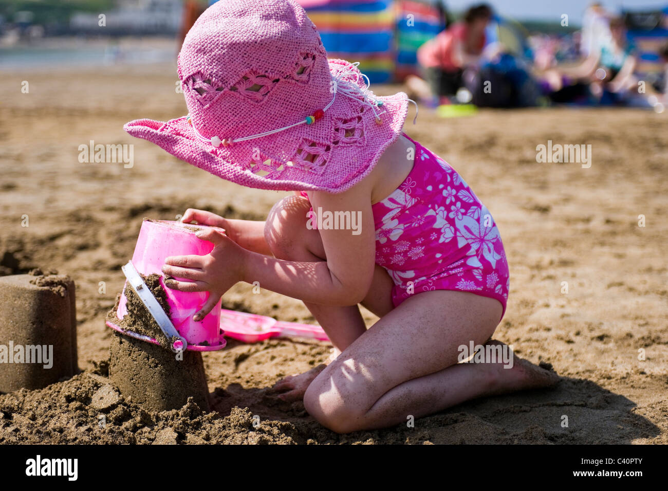 Horizontal portrait of a little girl building sandcastles on the beach on a sunny day. - Stock Image