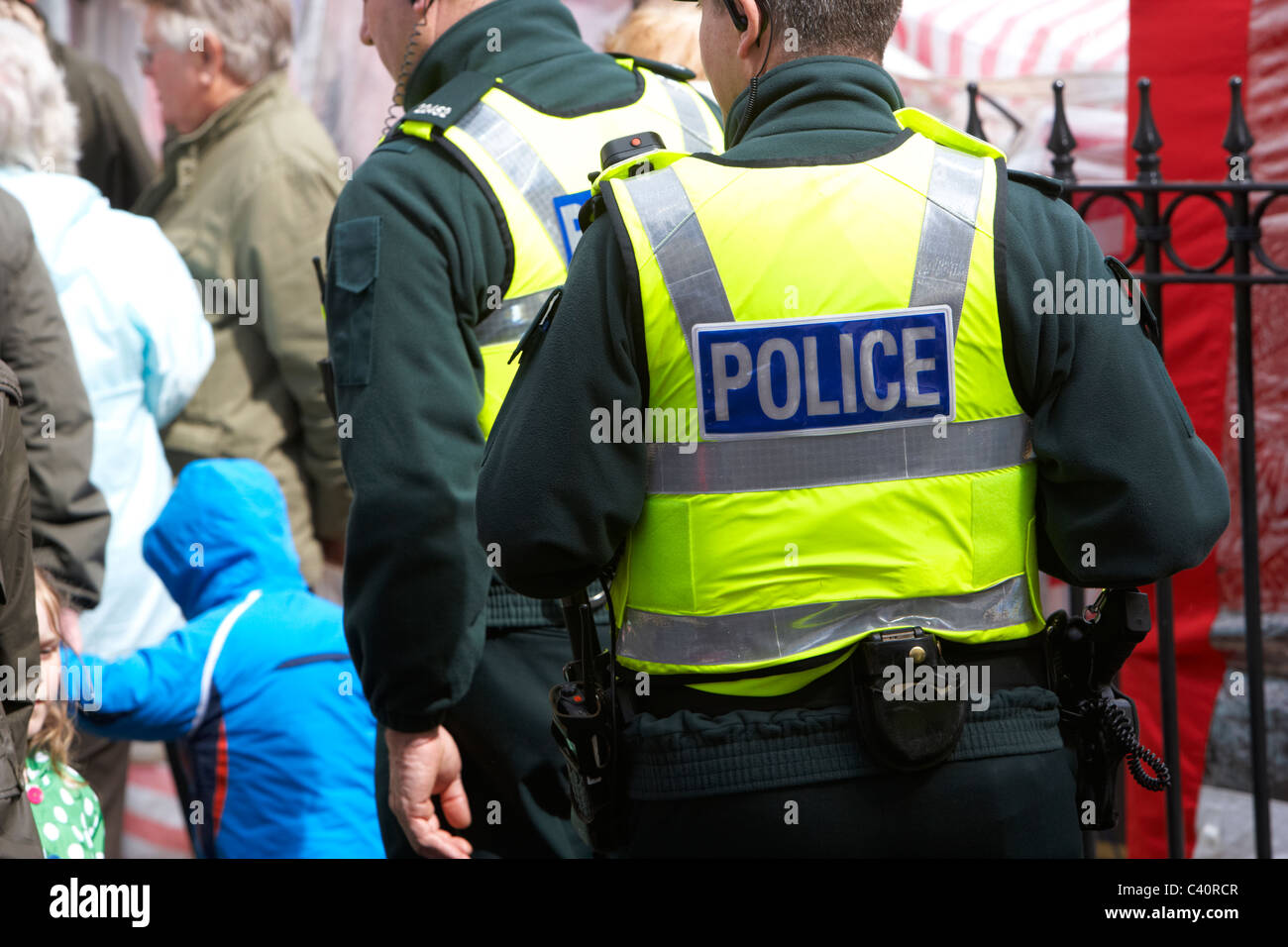 armed police officers wearing stab proof bulletproof vests walk through the crowd - Stock Image