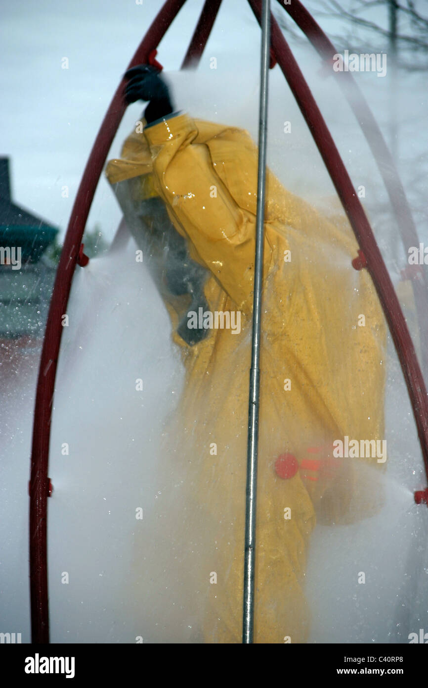 Firefighter practices using a decontamination shower - Stock Image