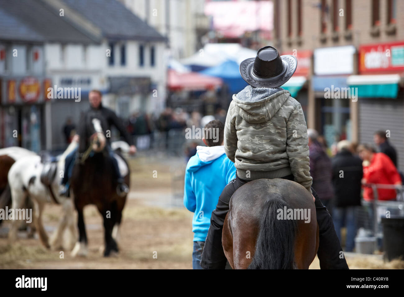 man in cowboy hat riding horse down main street during ballyclare may fair county antrim northern ireland - Stock Image