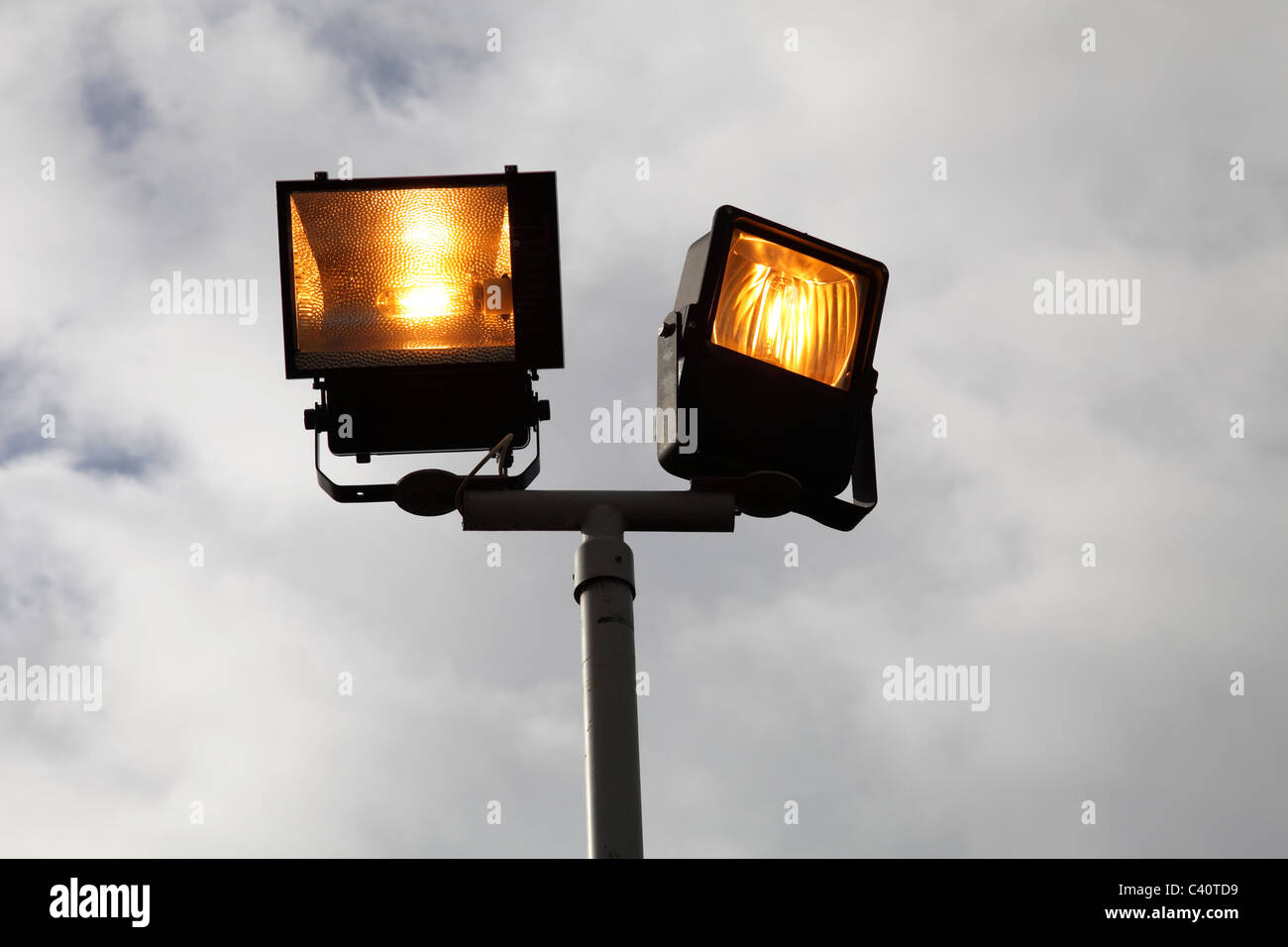 Lights on in daylight at business premises in the U.K. - Stock Image