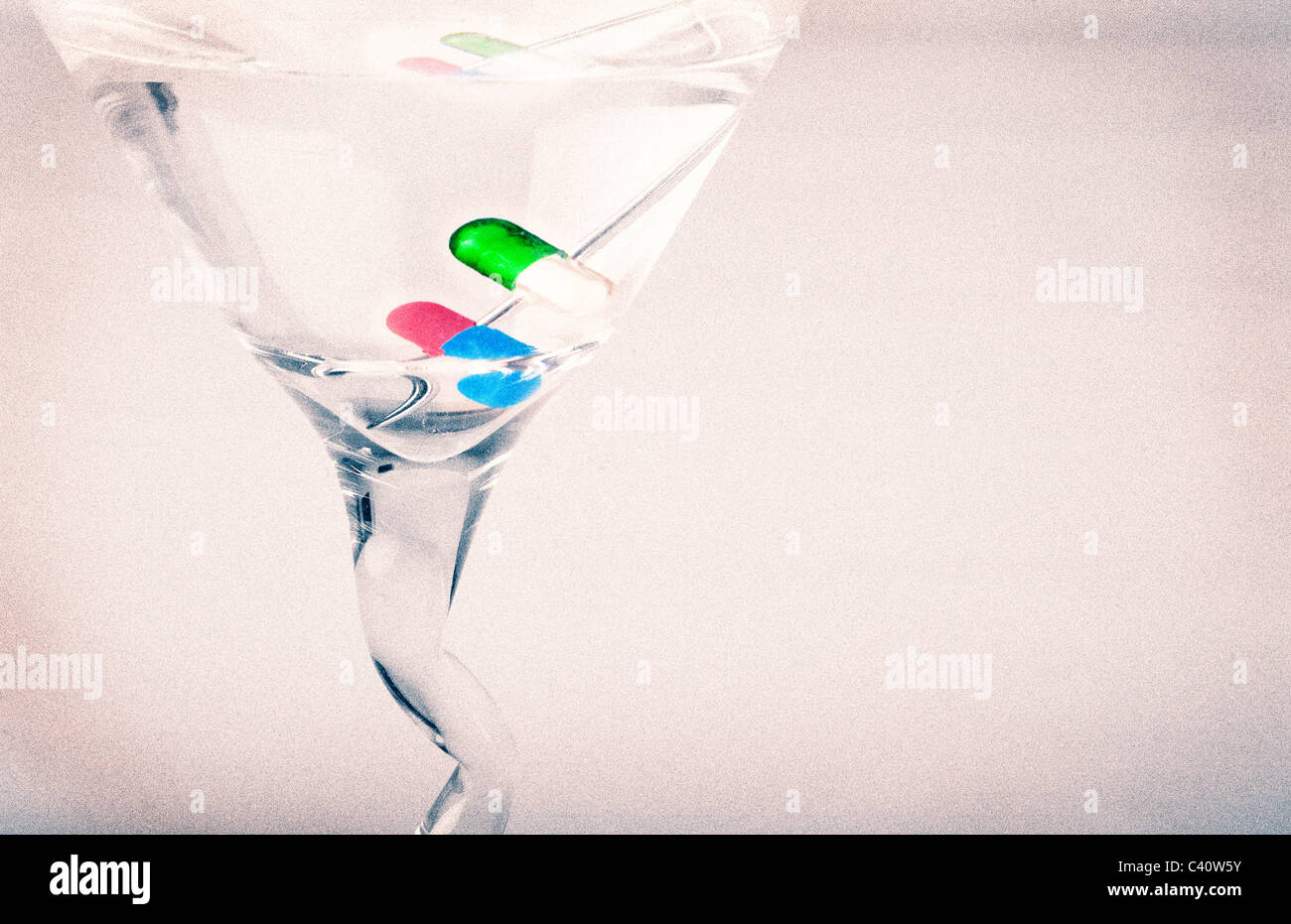 Martini with pill capsules for a garnish. - Stock Image