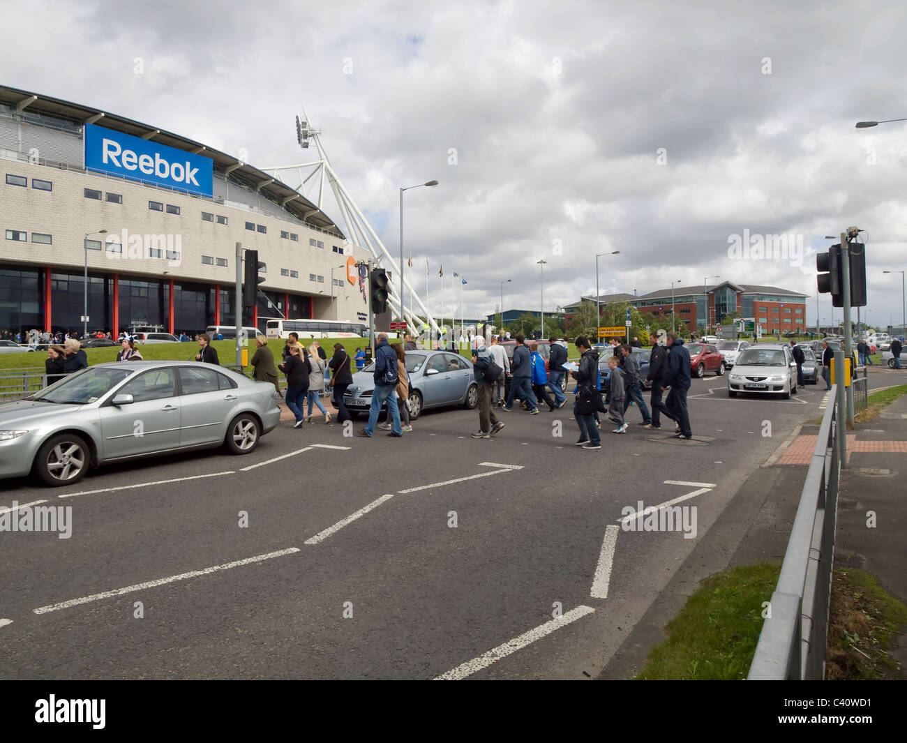 Football fans crossing the road going to the match at the Reebok Stadium, the home ground of Bolton Wanderers football Stock Photo
