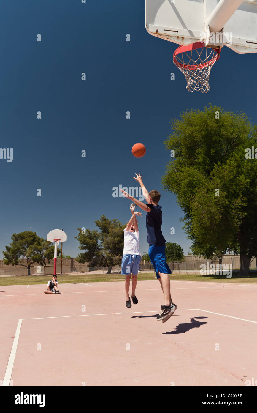 Boys playing basketball at an outdoor neighborhood park one boy looks on waiting his turn to play - Stock Image
