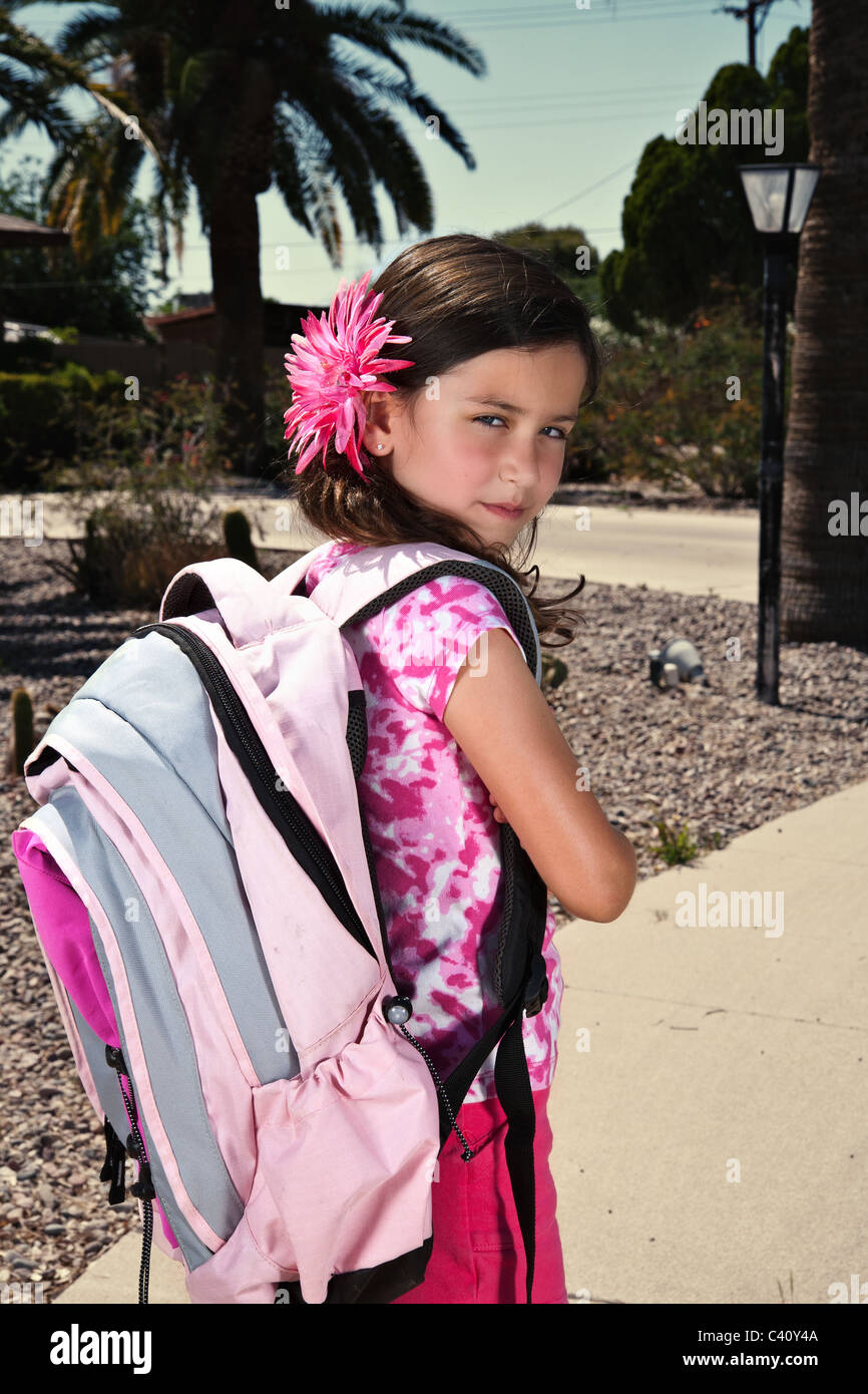 a young girl with her backpack on and looking over her should with a sassy look - Stock Image