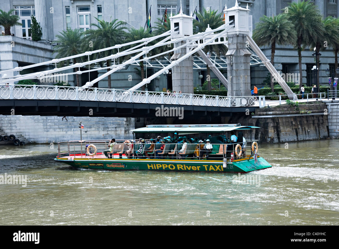 Hippo River Taxi with Tourists Passes Under Cavenagh Bridge on Singapore River Republic of Singapore Asia - Stock Image