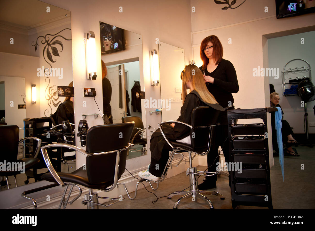 A young woman stylist cutting a teenage girl's hair in a hairdressing salon, UK - Stock Image