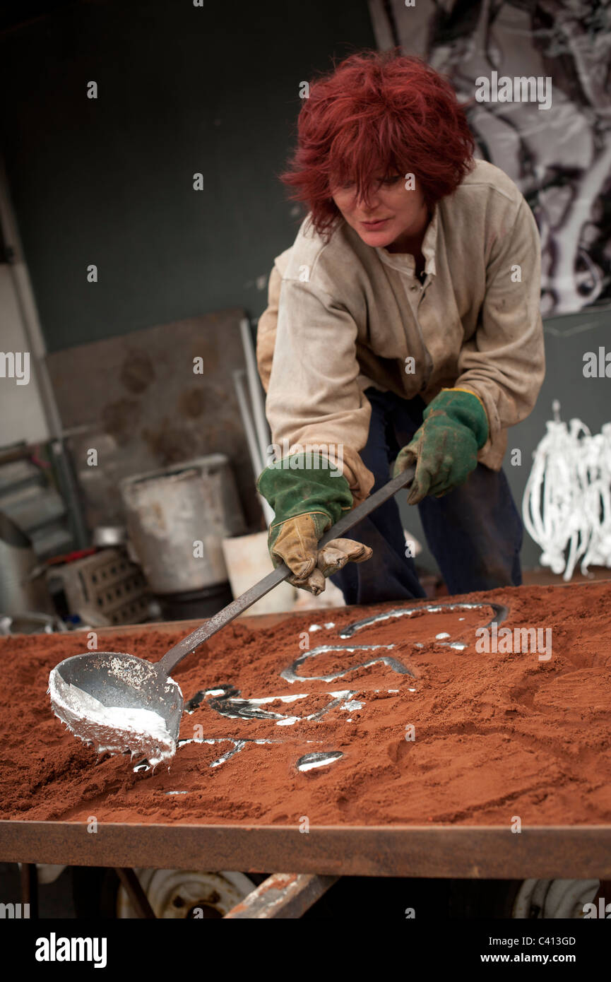 Artist DAWNY TOOTES Casting sculptures using molten aluminium made from scrap cans pots and pans, UK - Stock Image