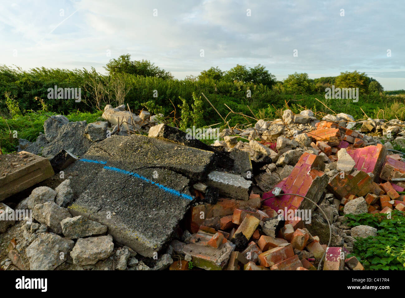 Illegally dumped rubble. Fly tipping of demolition waste in the countryside, Nottinghamshire, England, UK Stock Photo