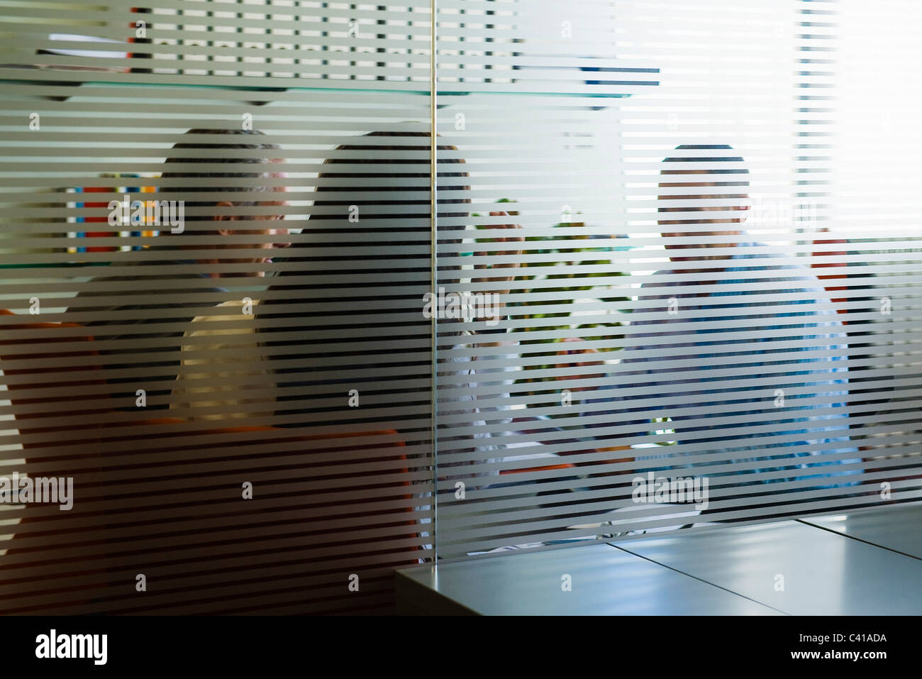 Meeting in office viewed through glass wall - Stock Image
