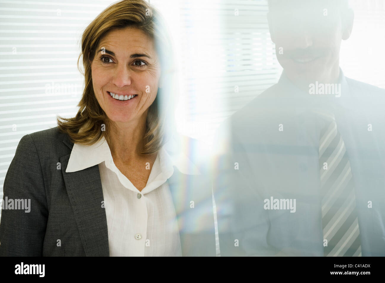 Smiling businesswoman looking away, businessman behind glass wall - Stock Image