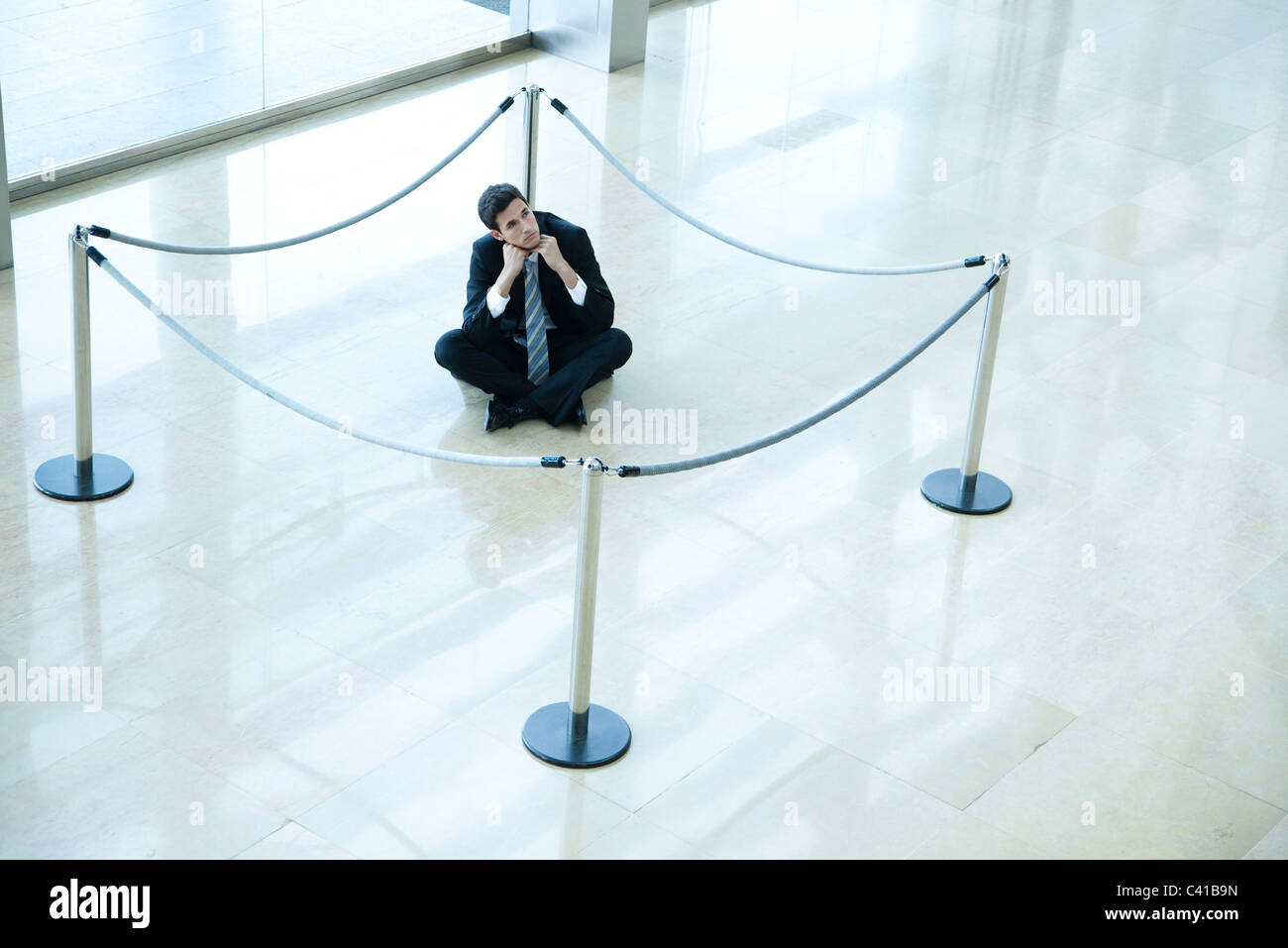 Businessman sitting on floor inside roped off area in lobby - Stock Image