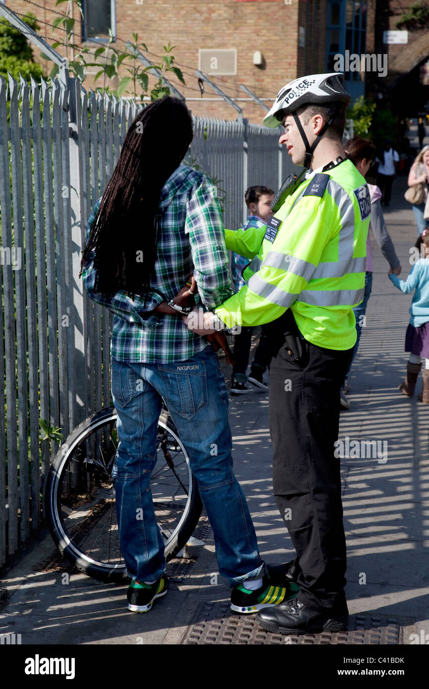 Black male being arrested after stop and search by a police officer in London, UK. - Stock Image