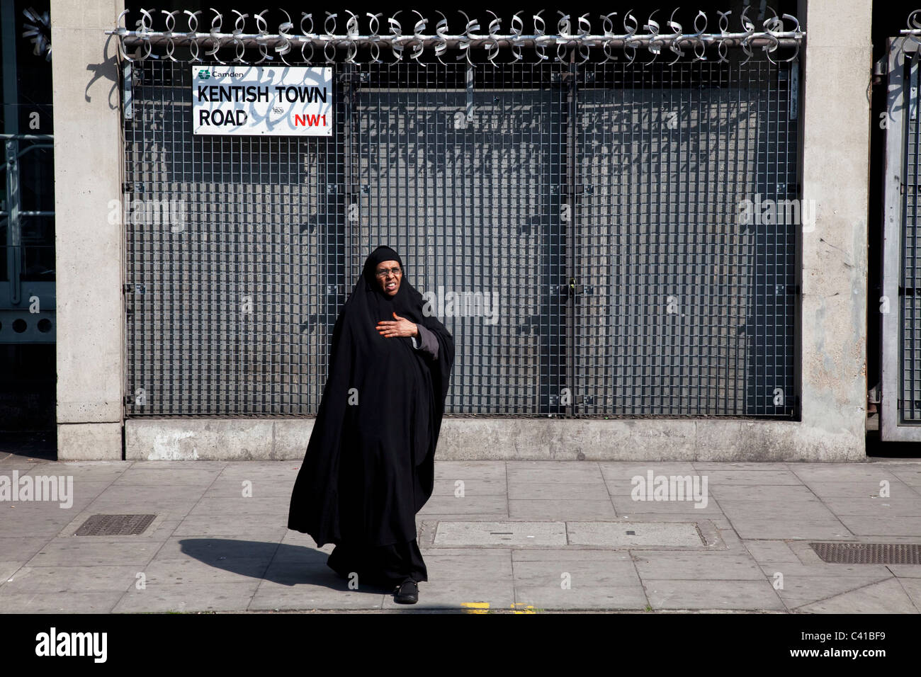 Muslim woman walks past heavily fortified gates, London. Security includes locks, barred doors and anti climb rotating Stock Photo