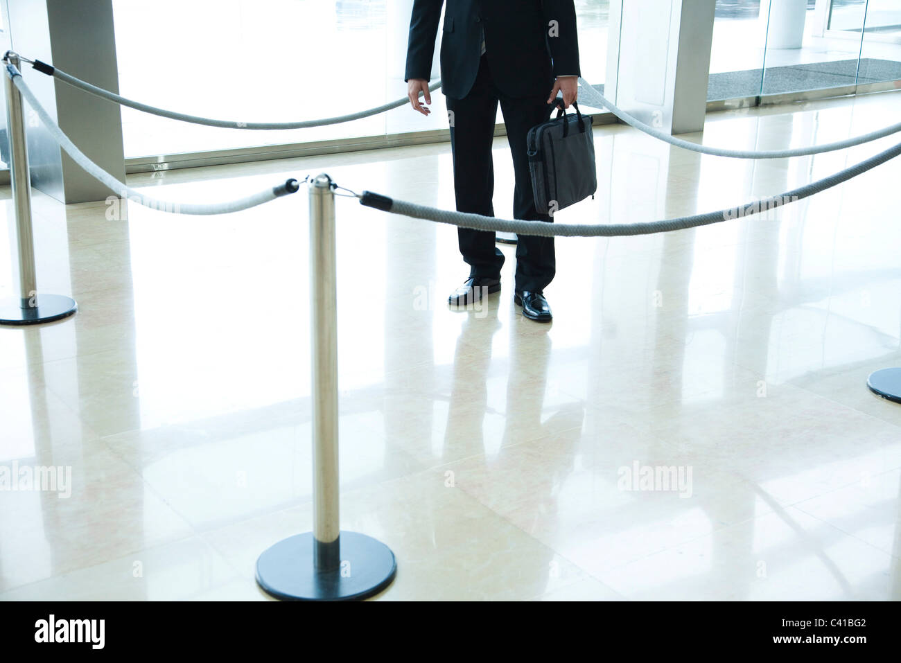 Businessman standing inside roped off area in lobby - Stock Image