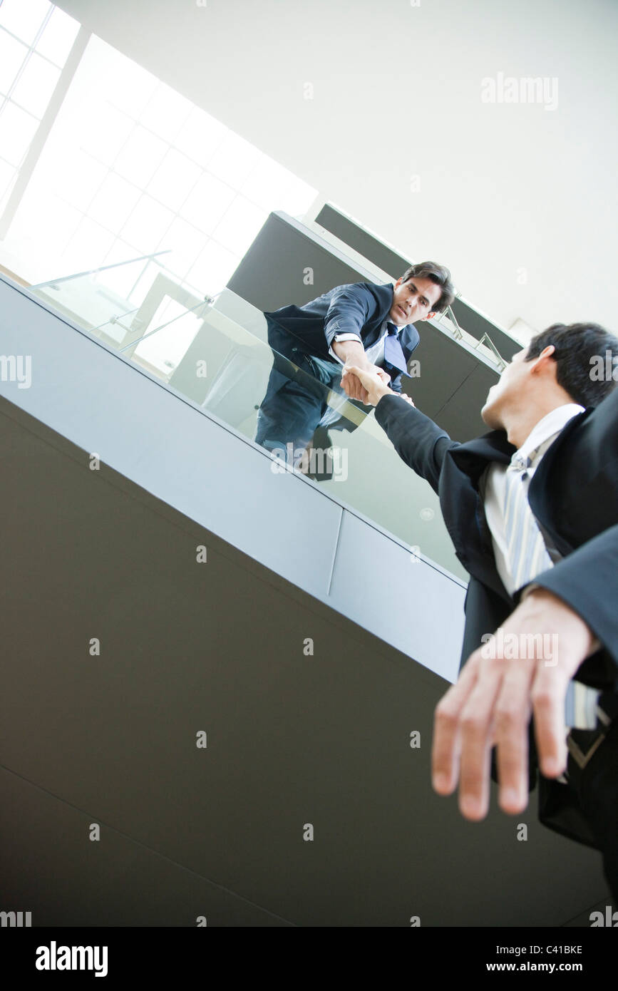 Businessman leaning over balcony, holding on to colleague's hand - Stock Image