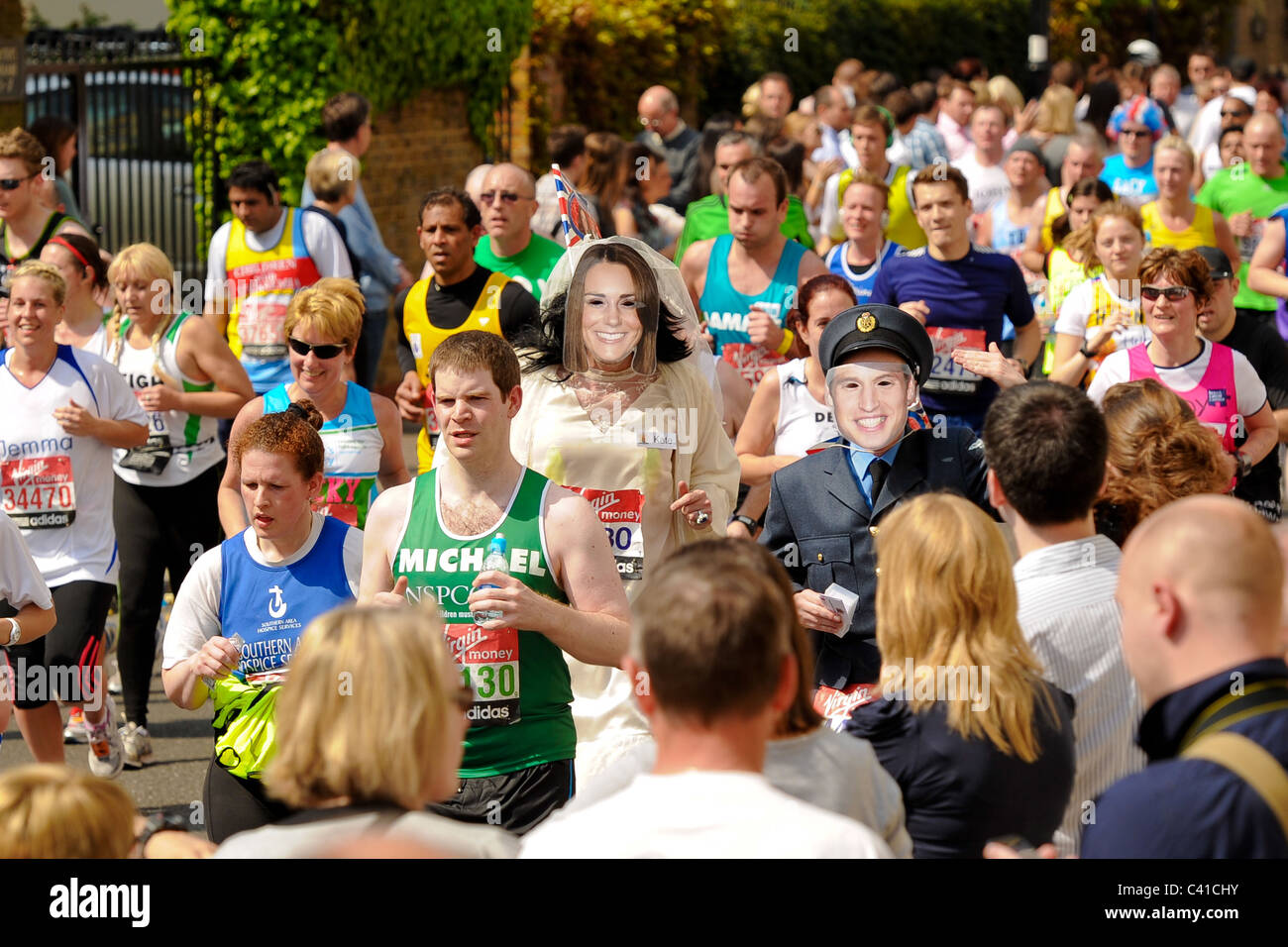 Runners take part in the Virgin 2011 London Marathon  with runners wearing mask of Prince William and Catherine Stock Photo