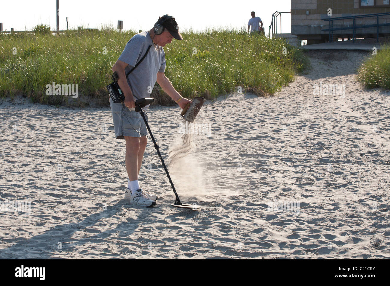 Searching the Sand. A man with a metal detector sifts through the sand at Long Beach Nahant just north of Boston. - Stock Image