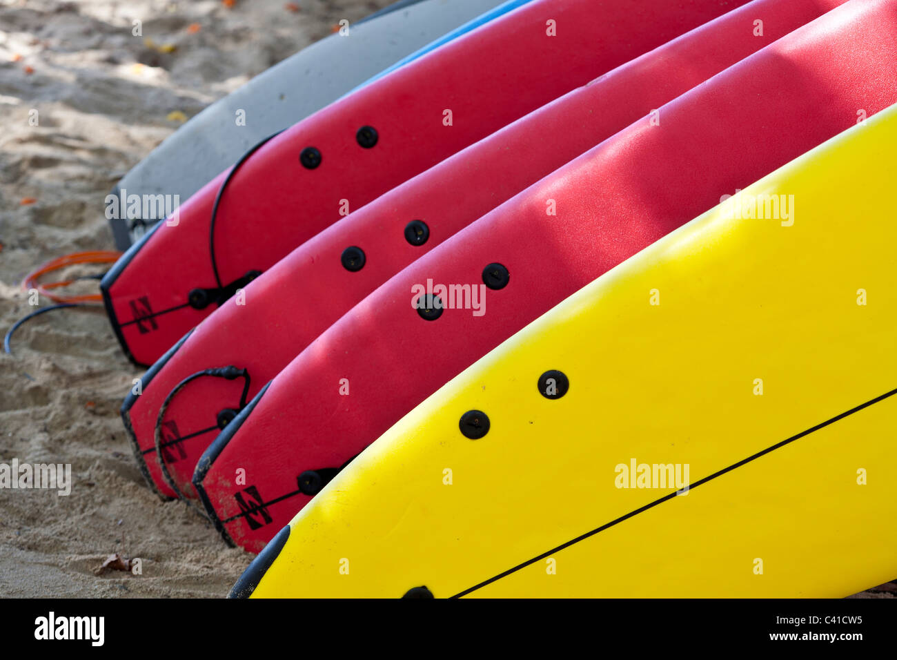 Ready for the Surf: Rental surfboards stacked on Waikiki beach. A collection of red and yellow surfboards await - Stock Image