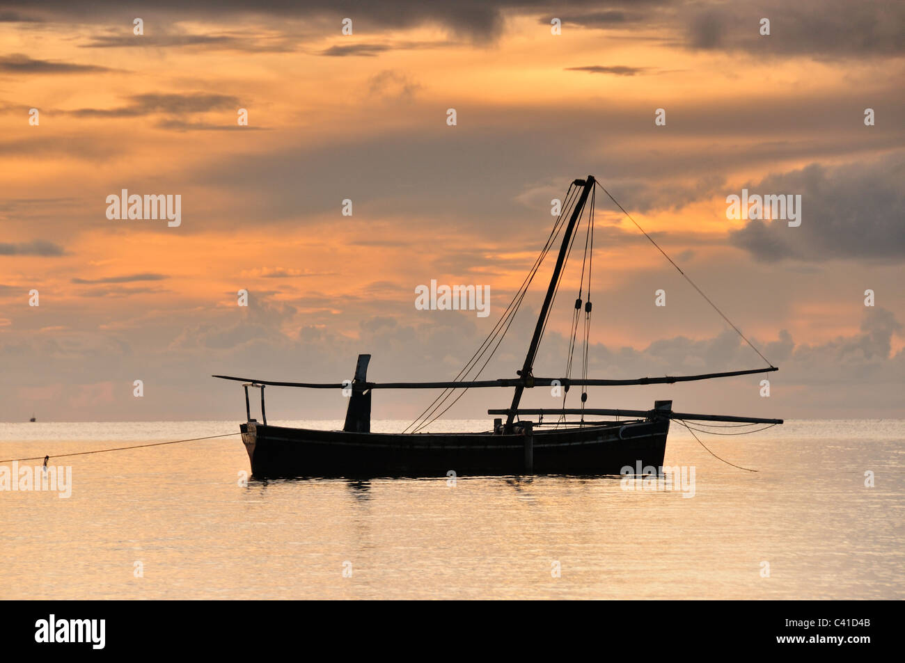 A Dhow in the Indian Ocean off the coast of Mafia Island, Tanzania at sunset - Stock Image