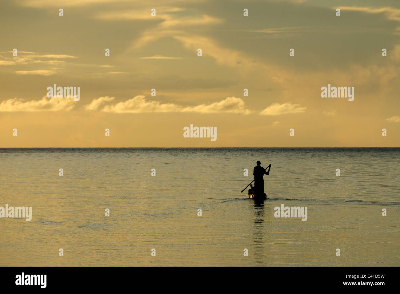 Fisherman punting a dugout canoe off the coast of Mafia Island, Tanzania - Stock Image