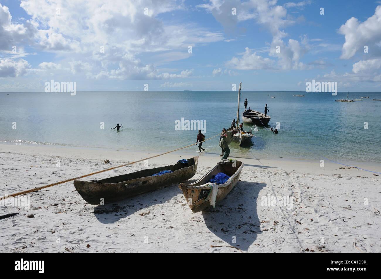 Fishermen landing their dugout canoes at 'Ras Mbisi' on the coast of Mafia Island, Tanzania - Stock Image