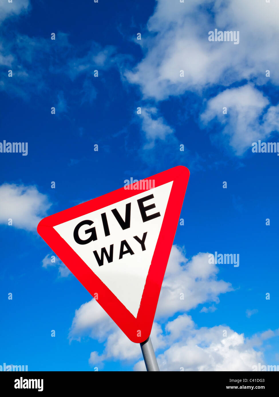 Give Way triangular warning sign on a UK road with blue sky and white clouds visible behind - Stock Image