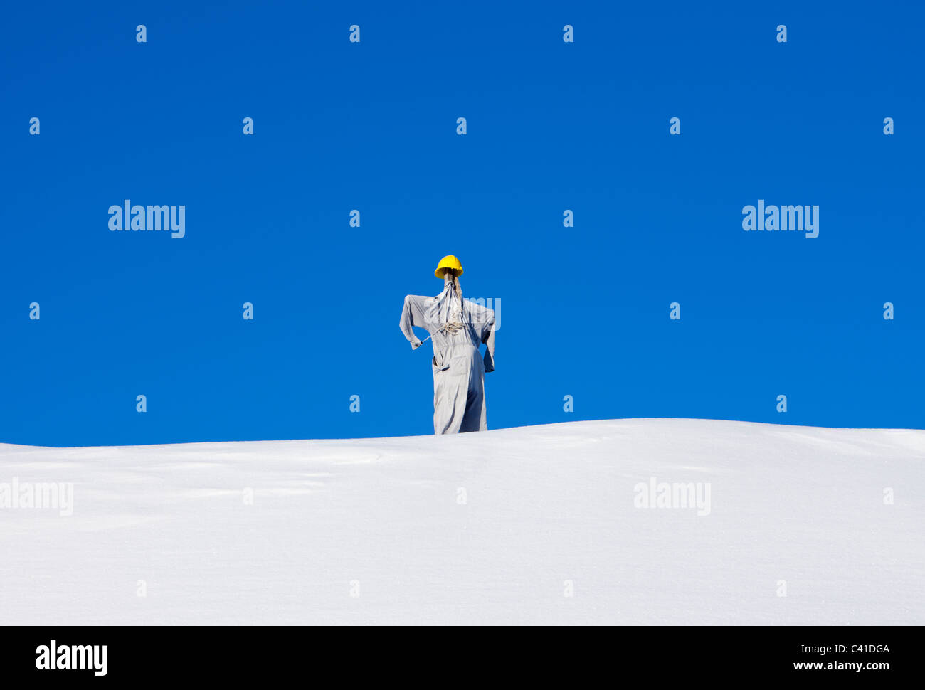 """""""Worker"""" scarecrow on top of a snowy hill Stock Photo"""