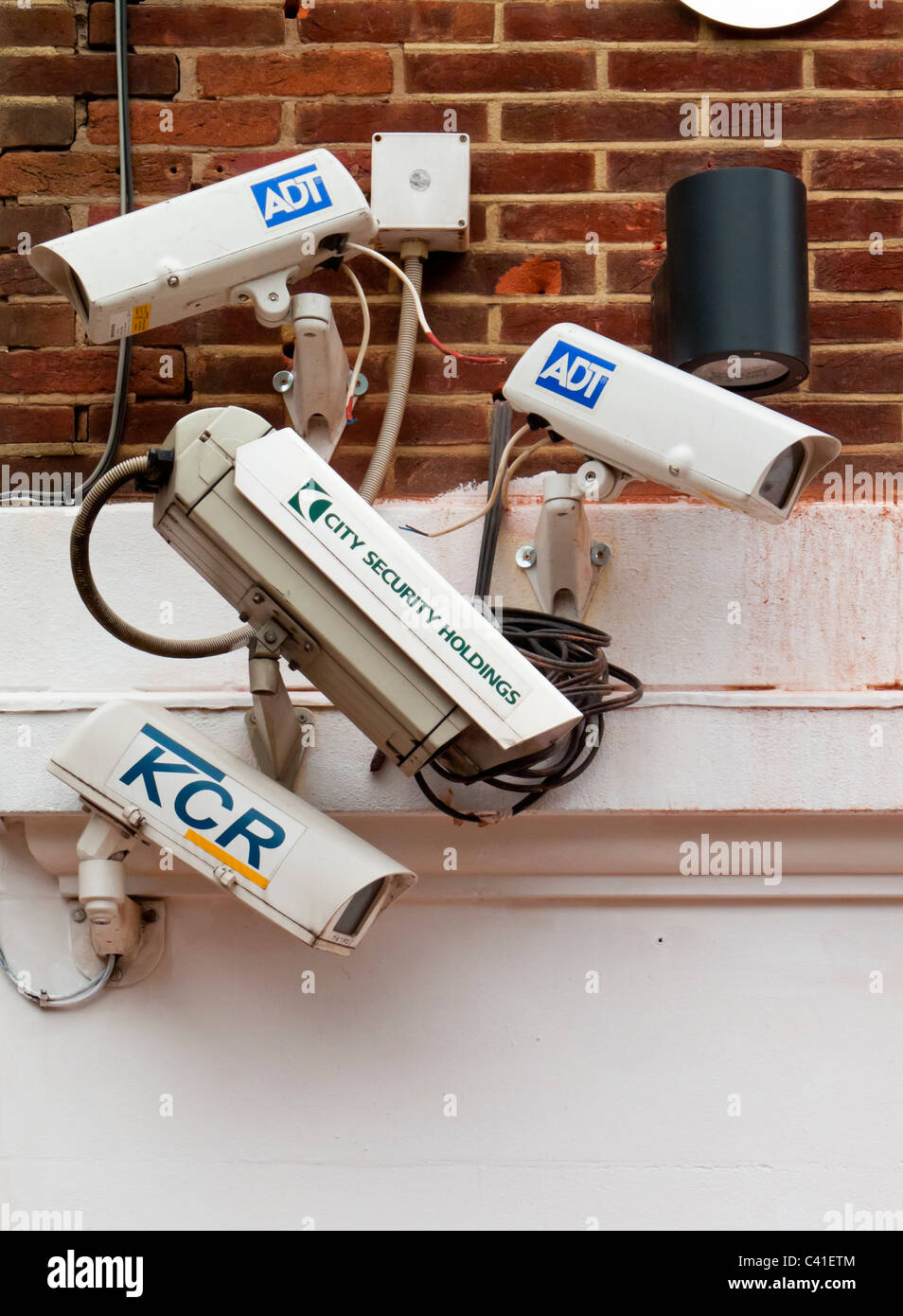 Group of four CCTV security cameras mounted on a wall in the UK Stock Photo