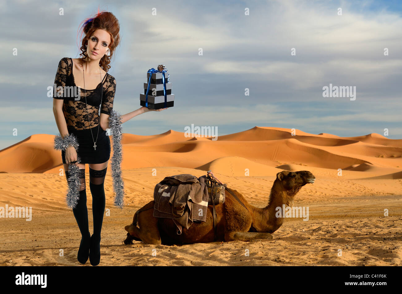 Woman with gifts and Dromedary camel Erg Chebbi desert gold sand dunes Morocco composite - Stock Image