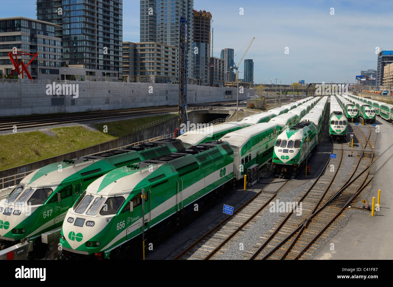 GO Train commuter railroad cars lined up on downtown Toronto tracks waiting to come in to Union Station for rush - Stock Image