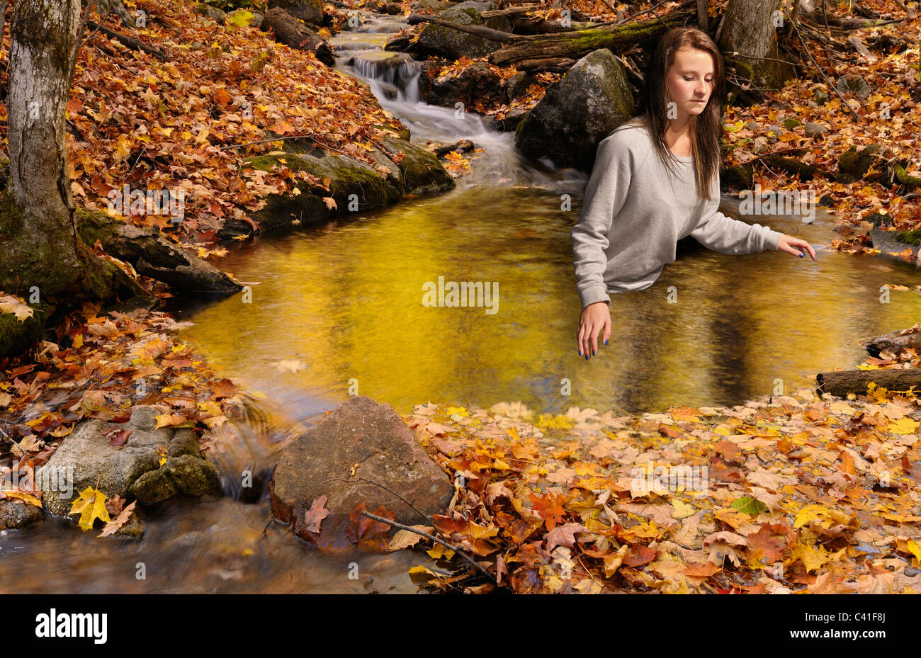 Girl rising from a Golden pond on the Blanchet Trail Gatineau Park in the Fall Quebec composite - Stock Image