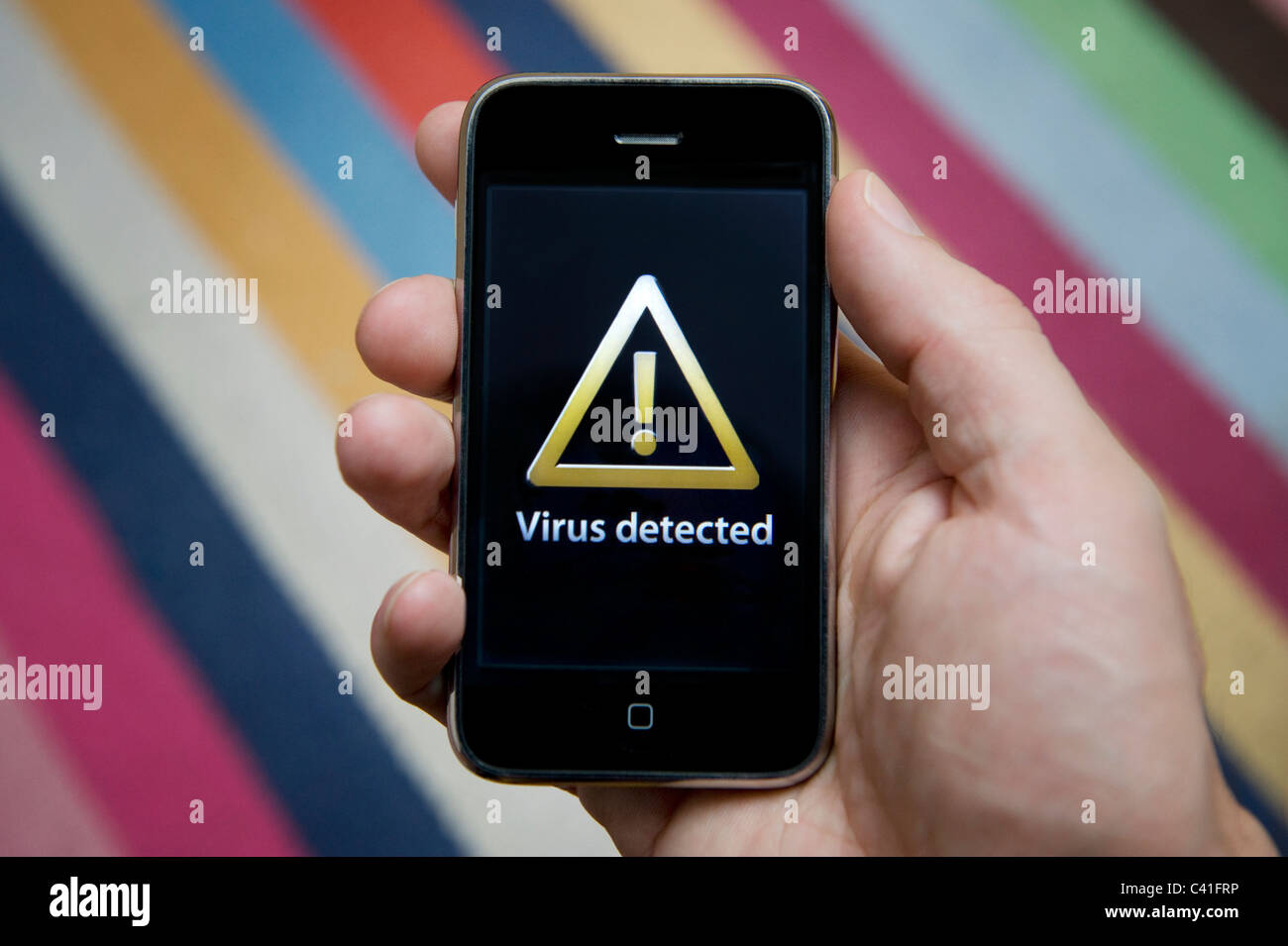 Close up of male hand holding an iPhone which is indicating the detection of a virus. (Editorial use only). - Stock Image