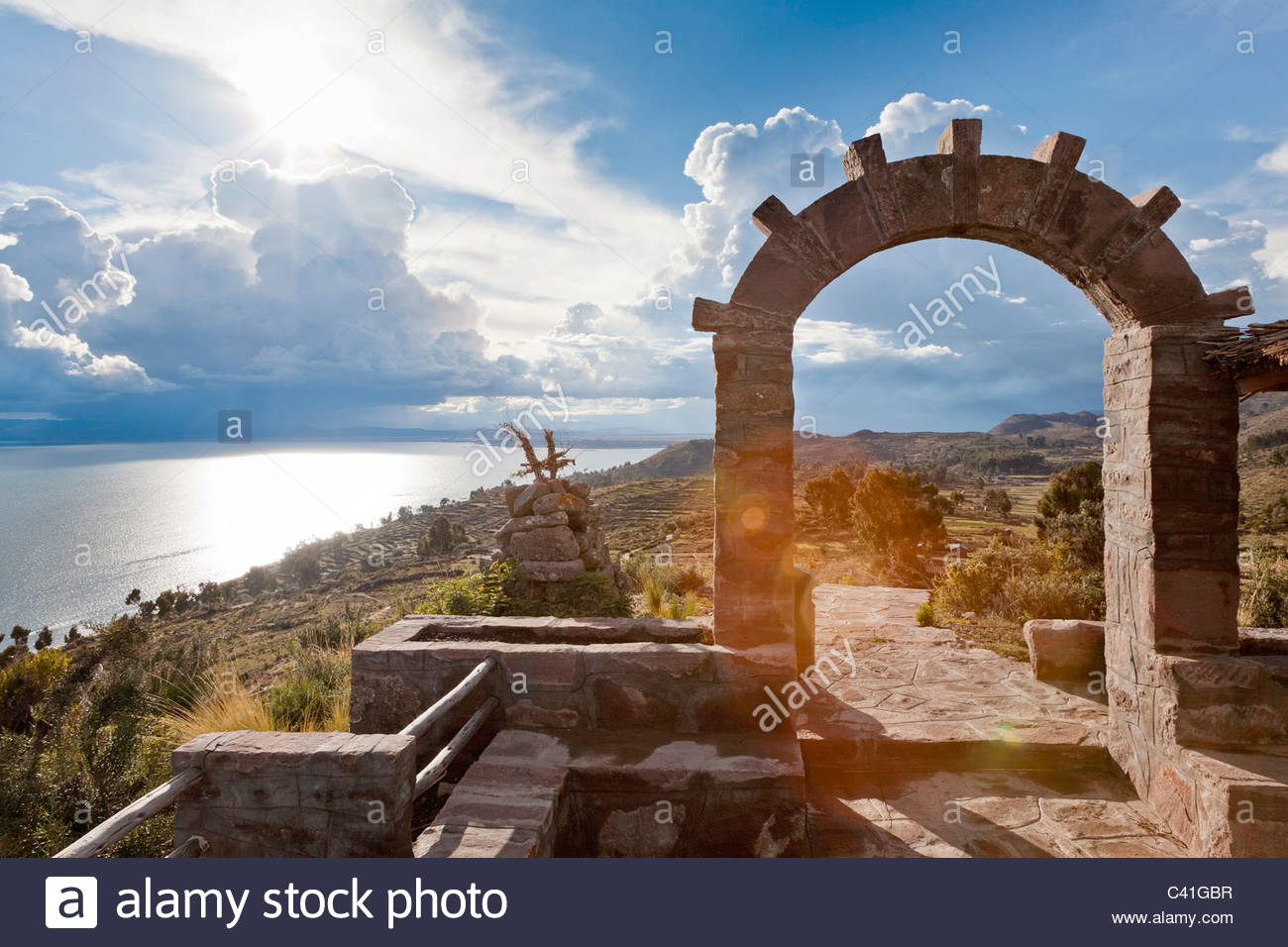 A stone archway with a dramatic sky as the sun sets. Lllachon, Capachica Peninsula, near Puno, Peru. - Stock Image