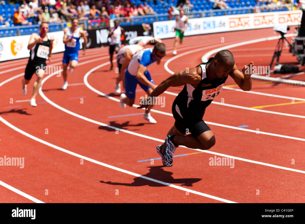 High resolution image of some sprinters starting to take the baton at athletics event. - Stock Image