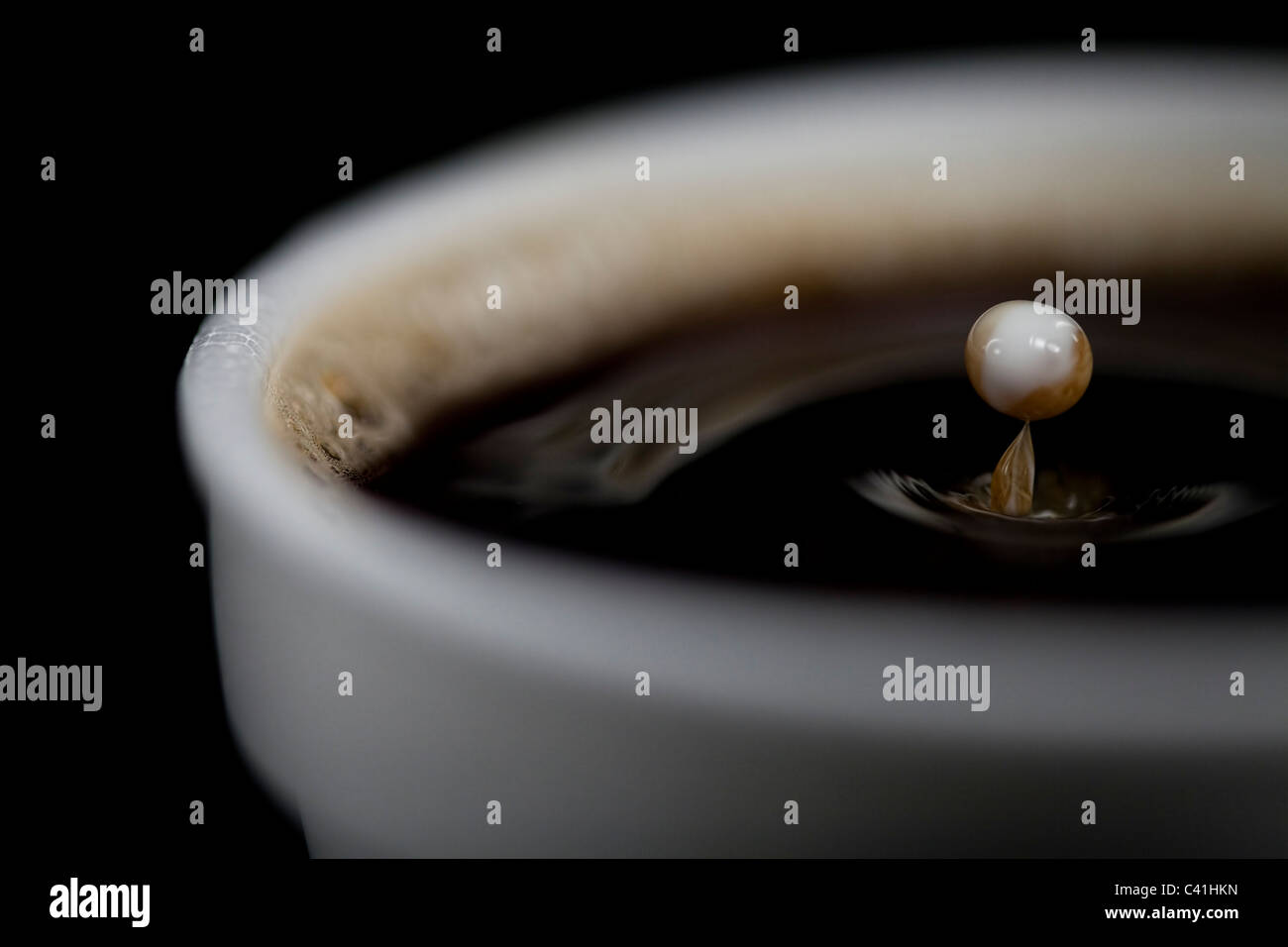 Milk drop in cup of coffee - Stock Image