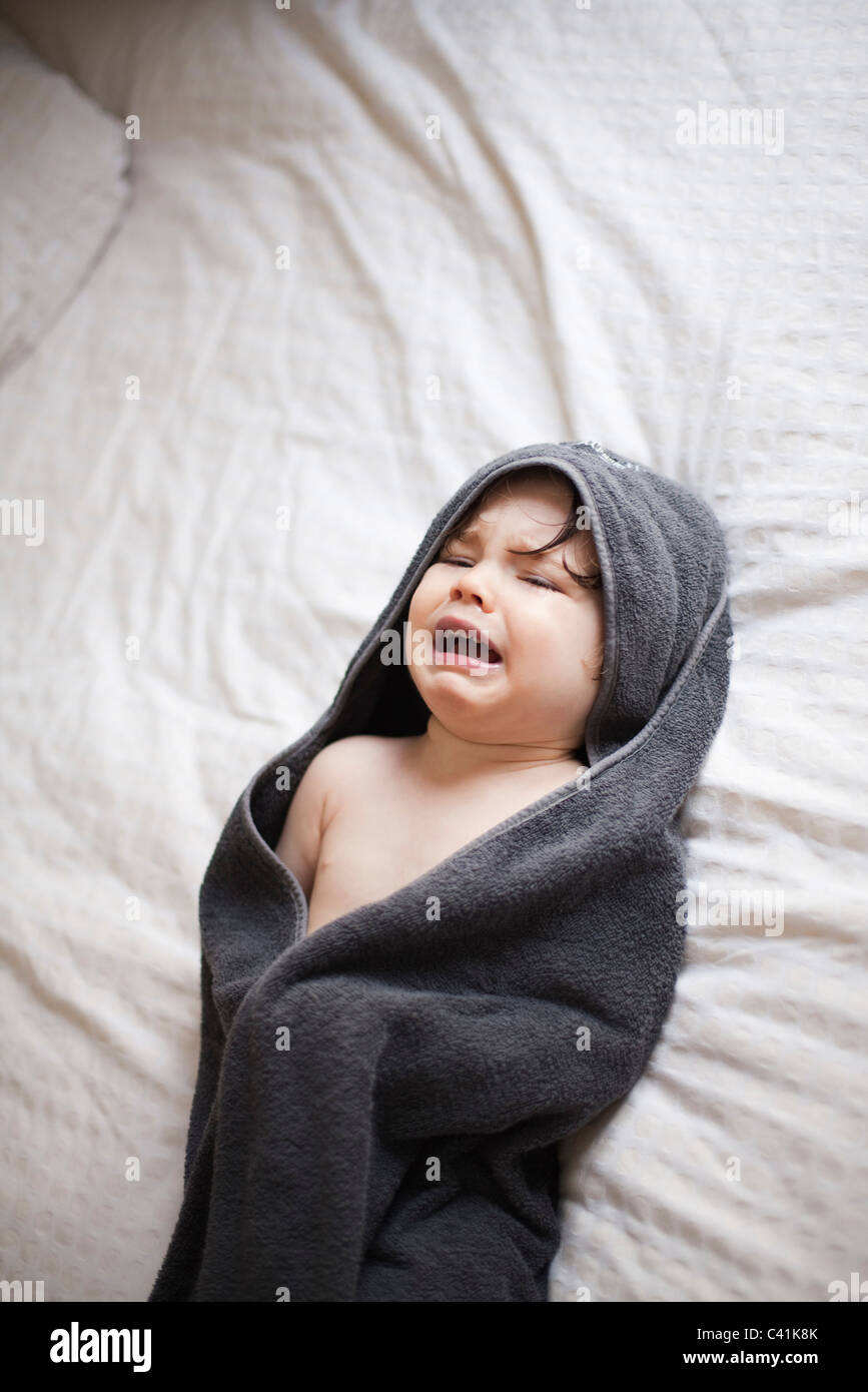 Crying toddler wrapped in a towel after bath - Stock Image