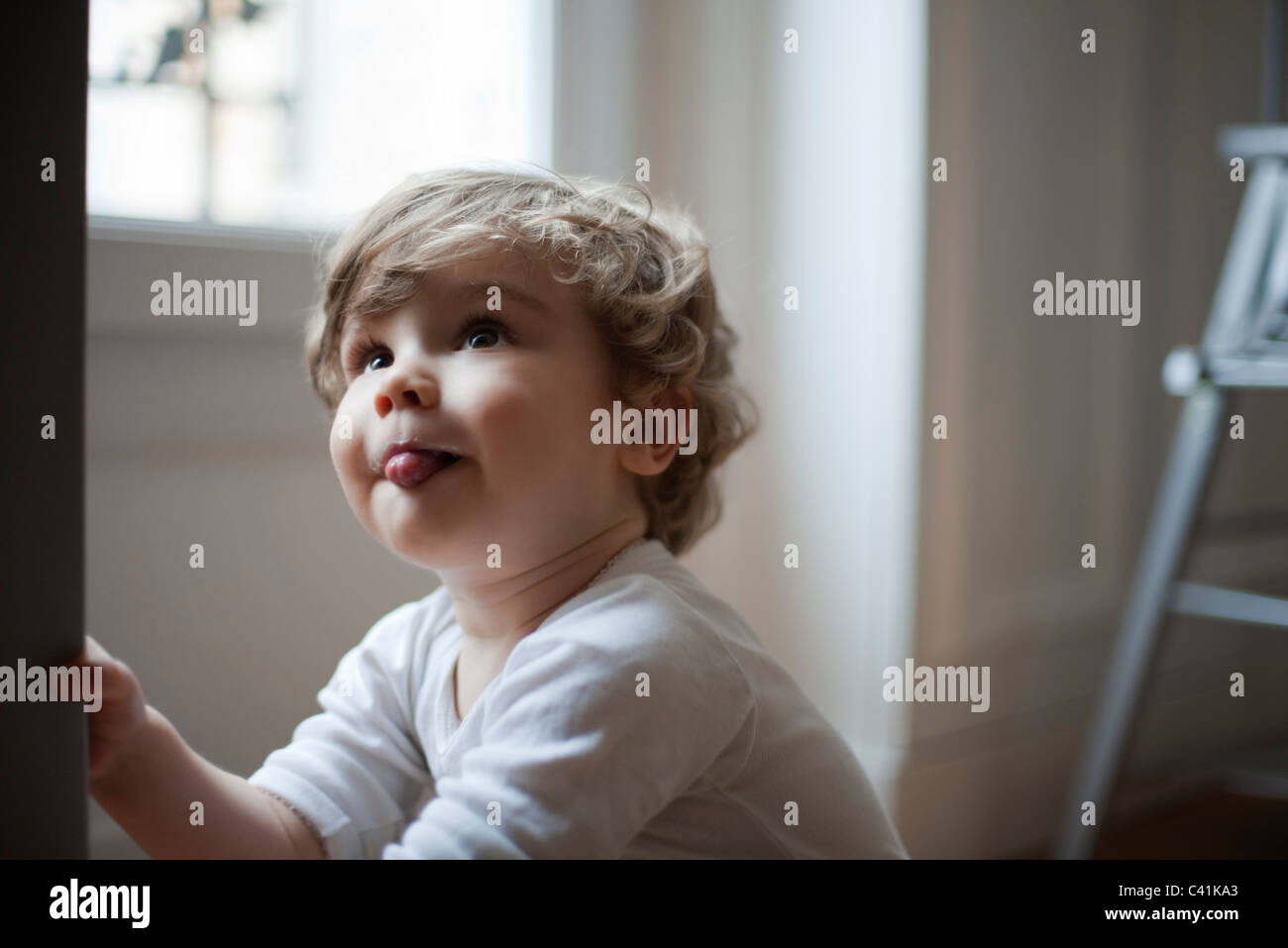 Toddler boy sticking out tongue, looking up, portrait - Stock Image