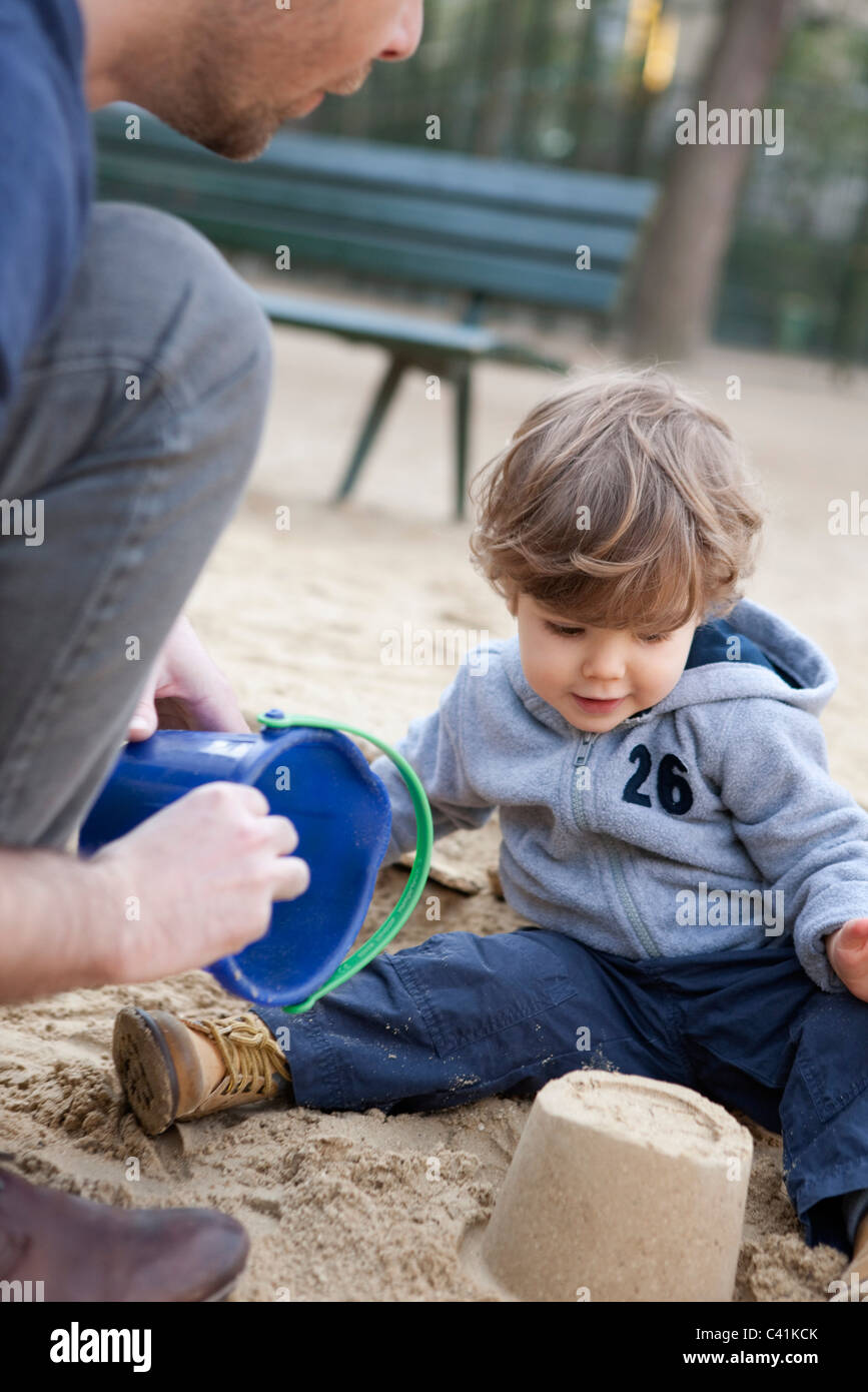 Toddler boy playing in sand with his father - Stock Image
