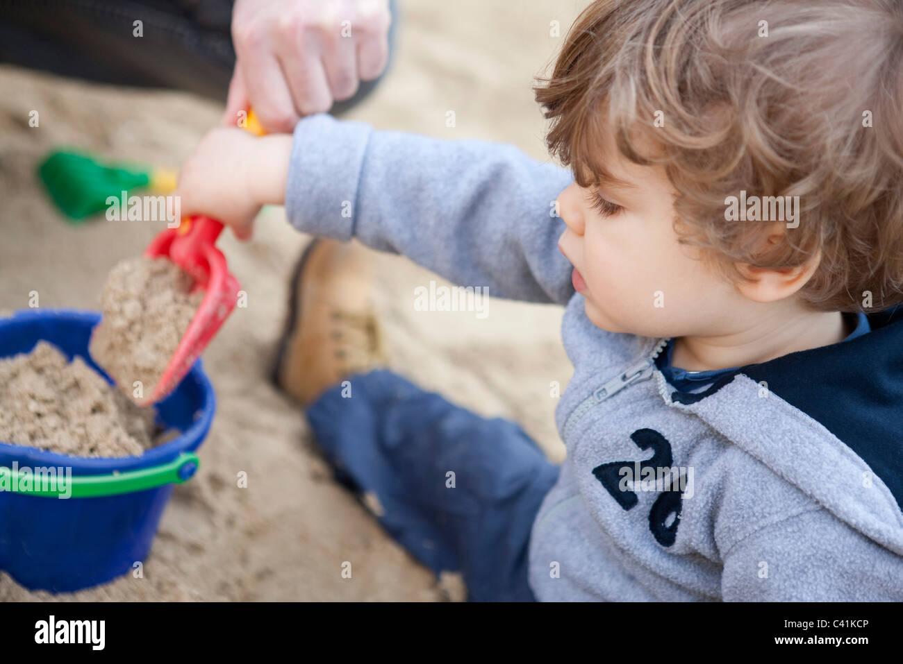 Toddler boy shoveling sand into bucket - Stock Image