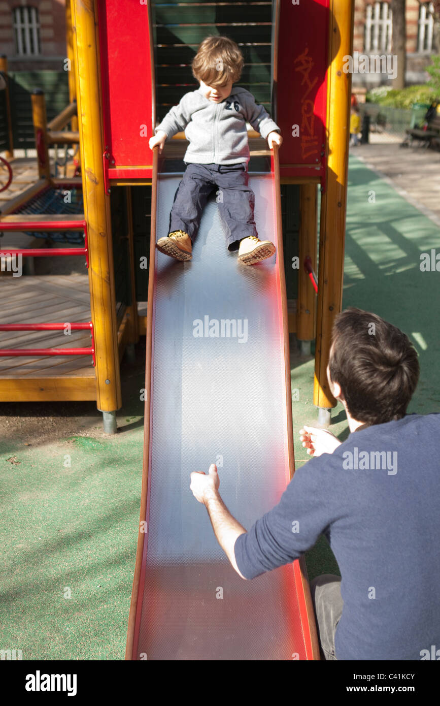 Toddler boy preparing to go down playground slide, father waiting at the bottom Stock Photo
