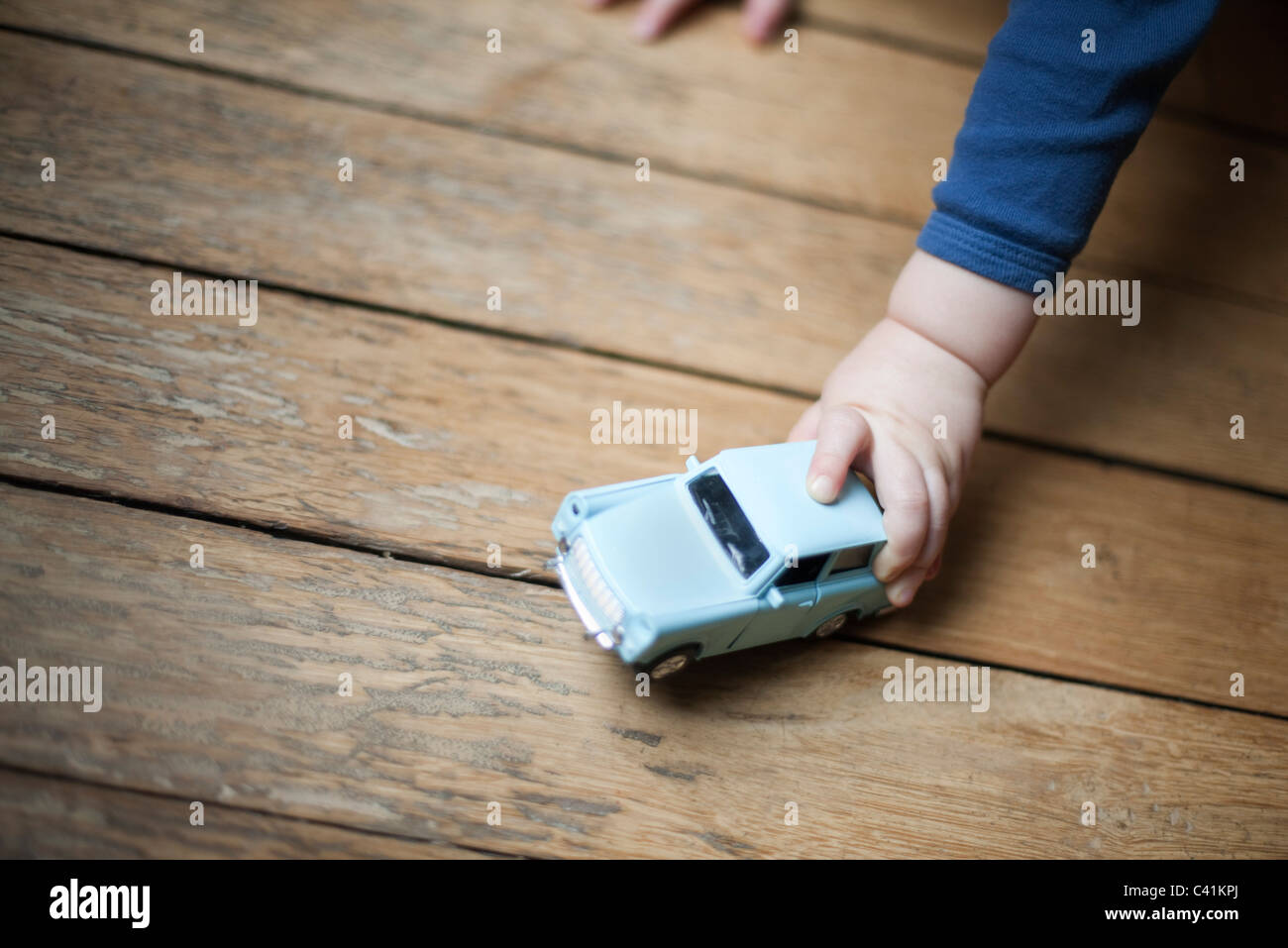 Child's hand holding toy car Stock Photo