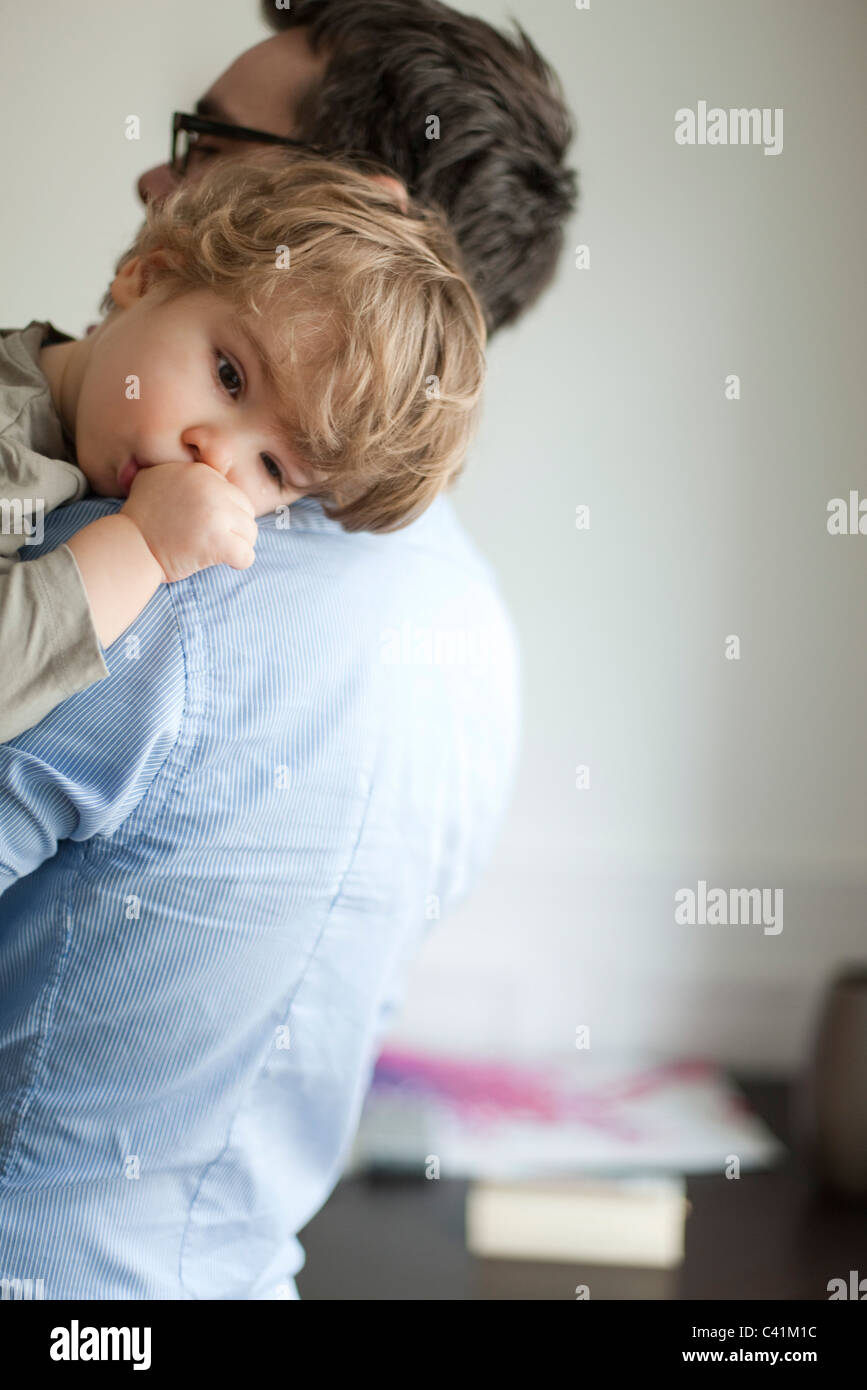 Toddler boy resting head on father's shoudler - Stock Image
